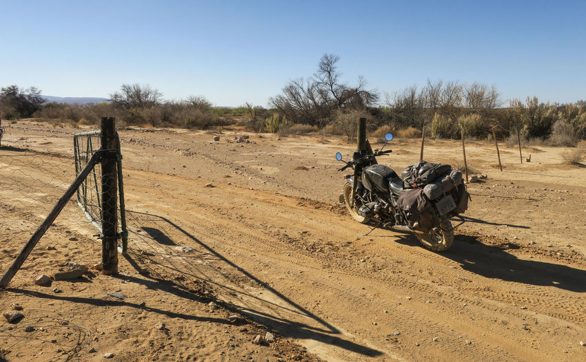 Motorcycle loaded with luggage and gear parked at open gate Adventure Arid Climate Clear Sky Day Desert Dirt Road Explore Gate Journey Land Vehicle Landscape Luggage Mode Of Transport Motorbike Motorcycle Nature No People Outdoors Riding Sand Sunlight Sunny Transportation Travel Let's Go. Together.