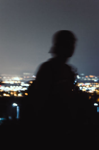 Rear view of silhouette man against illuminated city at night