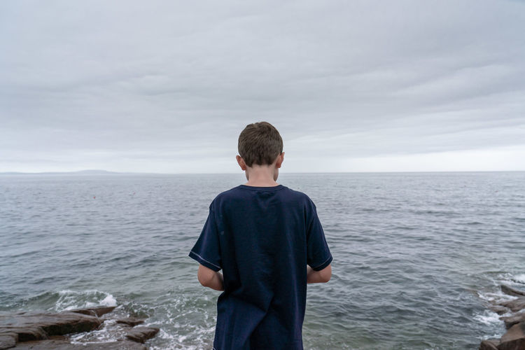 Boy by the water Adolescence  Beauty In Nature Blue Boys Child Horizon Horizon Over Water Leisure Activity Lifestyles Looking At View Males  Men Nature One Person Real People Rear View Scenics - Nature Sea Sky Standing Teenage Boys Teenager Waist Up Water