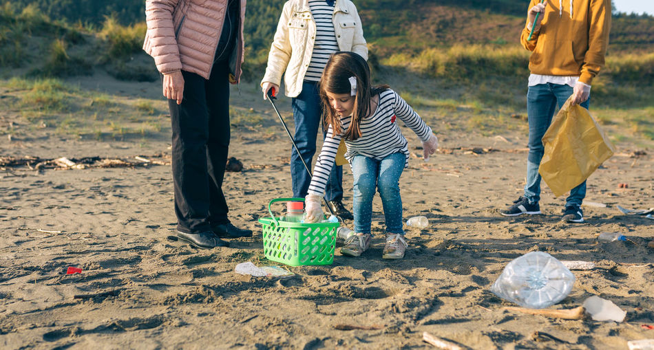 Girl putting plastic bottle into basket while standing at beach
