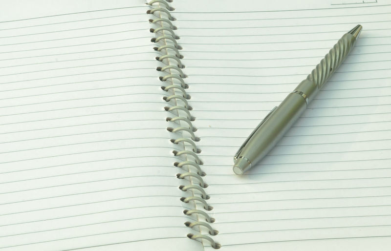 High angle view of pen on book against white background