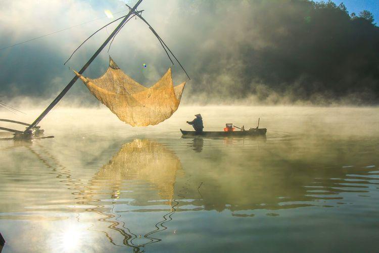 Men on fishboat in lake against sky