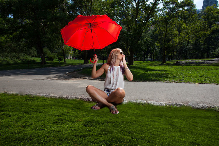Full length of woman with red umbrella sitting at park