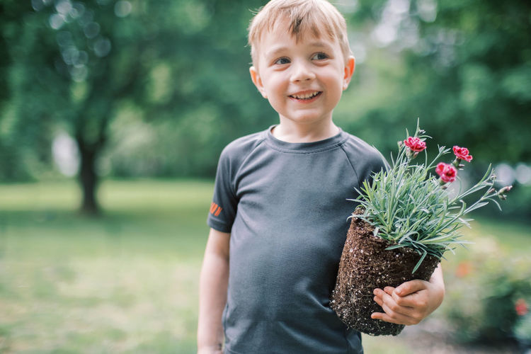 Cute boy smiling while standing by plants