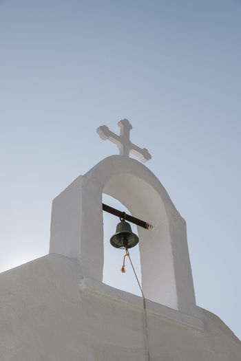 Low angle view of cross against building against clear sky