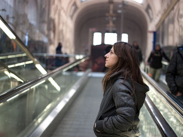 Side view of woman standing on moving walkway at milano centrale railway station