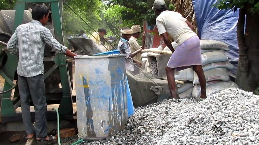 MAN AND MACHINE... CONSTRUCTION WORK... LABOUR... Hard Physical Workers Labourers Feed Gravel, Sand And Cement Gravel Work In Progress Labourers Construction Work Concrete Mixing Machine Men
