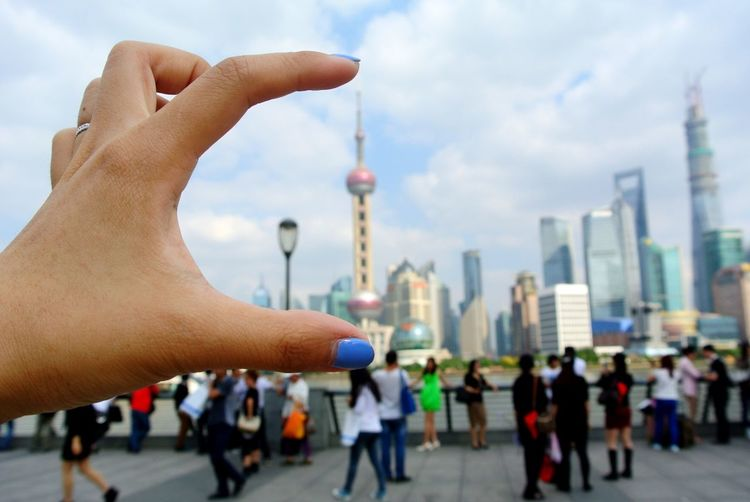 Optical Illusion Of Person Holding Oriental Pearl Tower In City