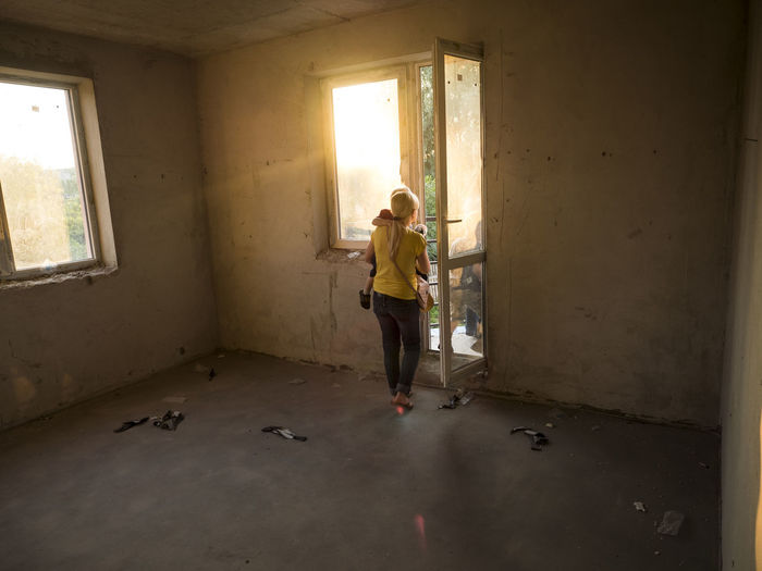 Young Caucasian woman with a boy at the hands of the new just bought an apartment Apartment Architecture Bad Condition Bought  Boy Built Structure Caucasian Damaged Day Deterioration Dirty Domestic Life Full Length Hands Home Interior In Front Of Indoors  Just New Obsolete People Wall - Building Feature Window Woman Young
