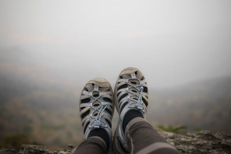 Low section of person wearing shoes against sky
