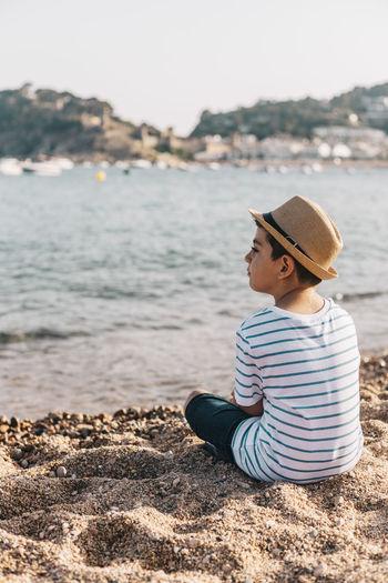 Side view of boy sitting on beach