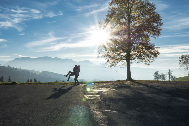 Man Lifting Woman Against Mountain On Sunny Day