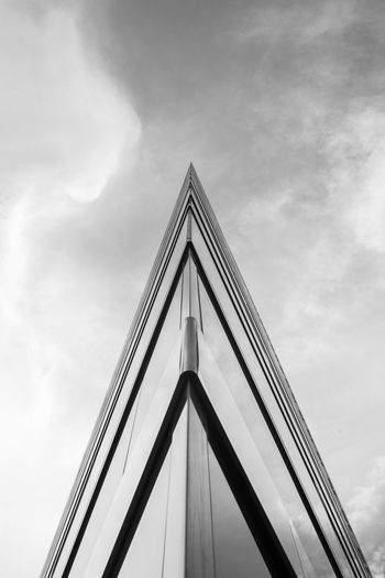 Low angle view of corner of a modern building pointing to cloudy sky; in black and white. Abstract Architecture Black And White Building Building Exterior Built Structure City Cloud - Sky Design Lines Low Angle View Metal Modern Office Building Penetrating Piercing Sharp Sky Statue Triangle