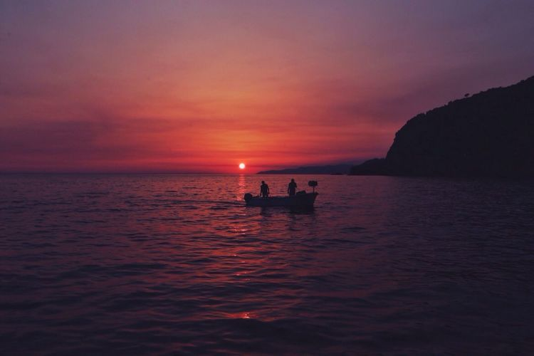 Silhouette of people on boat in sea