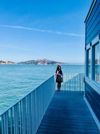 Rear view of woman on pier over sea against blue sky