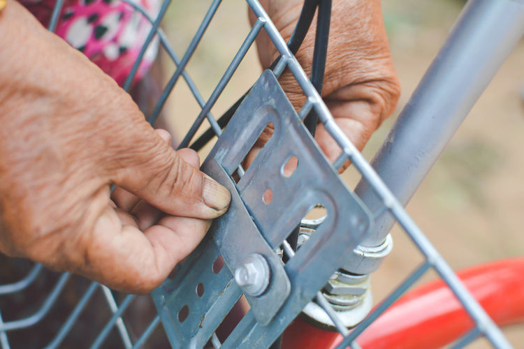 Close-Up Of Cropped Hand Fixing Bicycle Basket