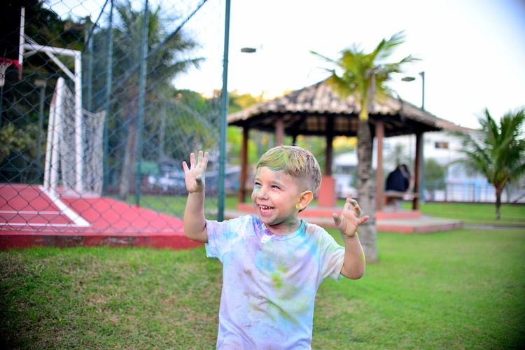 Cheerful Boy Covered With Colorful Powder Pain Standing At Park