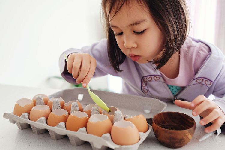 Close-Up Of Girl Putting Mud In Eggs Shells