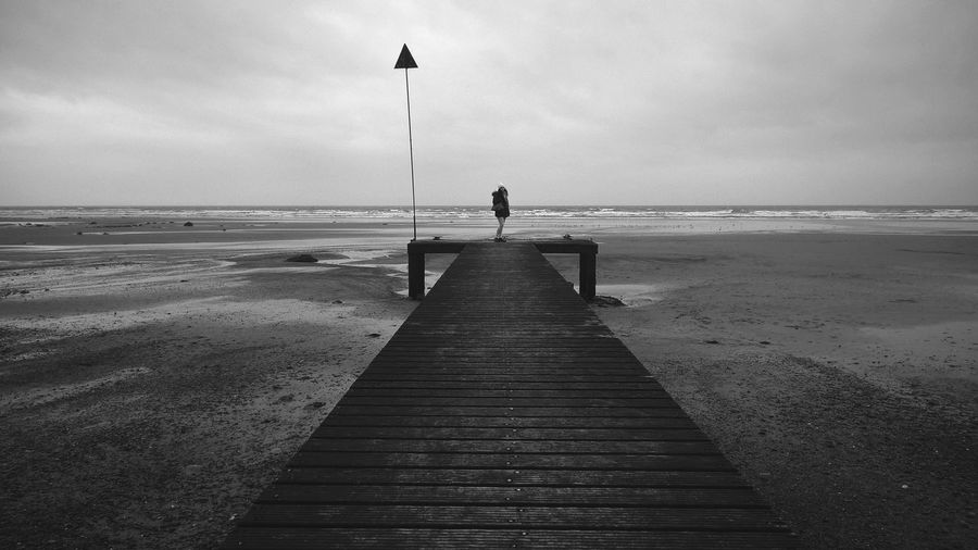 Low tide on a stormy day. EyeEm Best Shots EyeEm Gallery EyeEmNewHere Beach Beauty In Nature Cloud - Sky Day Horizon Over Water Jetty Leisure Activity Nature One Person Outdoors Pier Real People Sand Scenics Sea Sky Standing Tranquil Scene Tranquility Vacations Water Wood Paneling