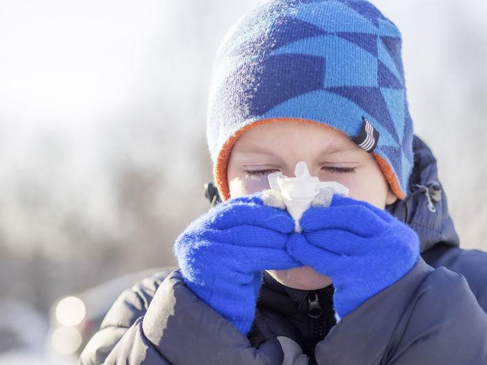 Close-up of boy sneezing