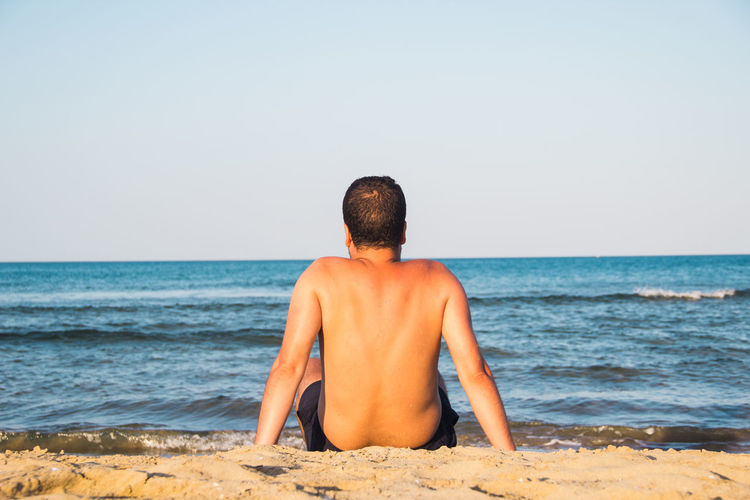 Rear view of shirtless man sitting at beach against clear sky