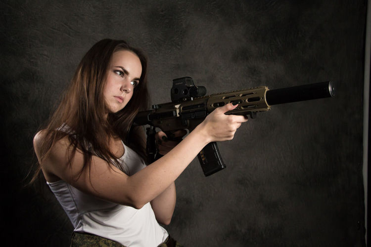 Adult Aggression  Aiming Beautiful Woman Black Background Brown Hair Clothing Gun Hair Hairstyle Handgun Holding Indoors  Long Hair One Person Portrait Studio Shot Teenager Waist Up Warning Sign Weapon Women Young Adult