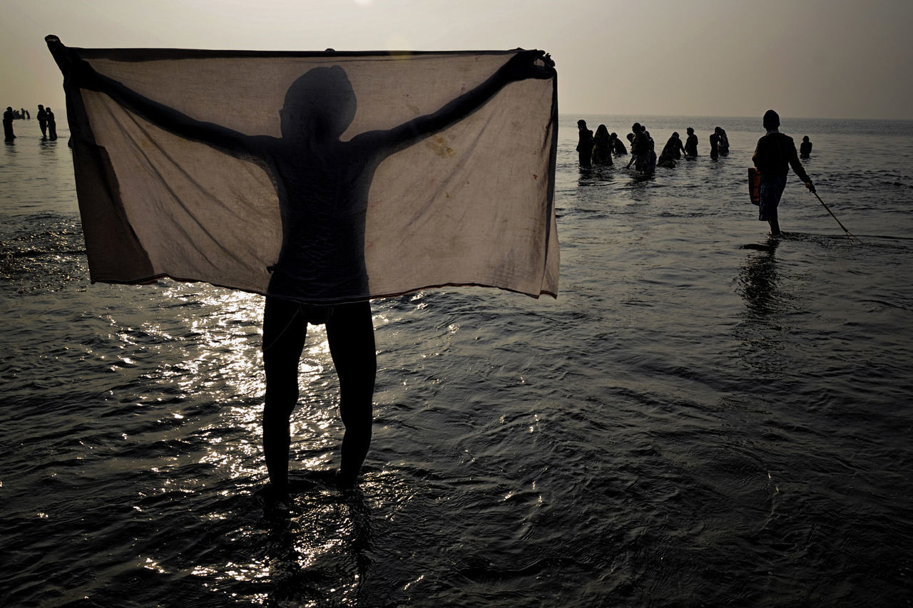 Silhouette man with textile standing against crowd at beach