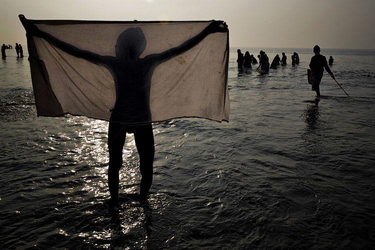 Rear view of silhouette people walking on beach