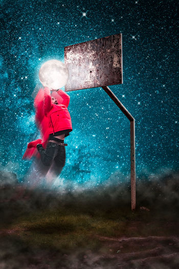 Optical illusion of man dunking moon in basketball hoop against sky