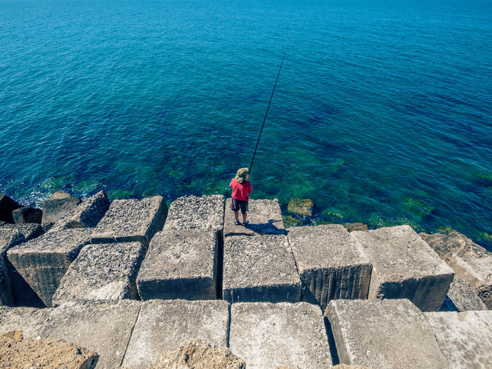 High Angle View Of Boy Fishing On Sea Shore