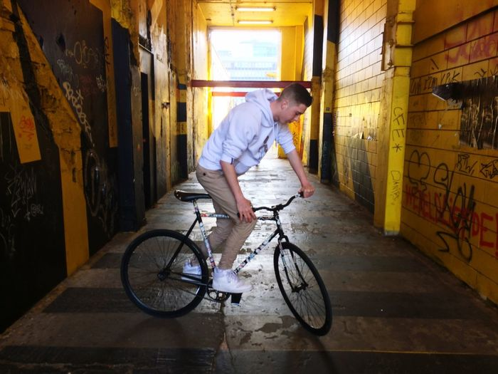 Young man riding bicycle in garage