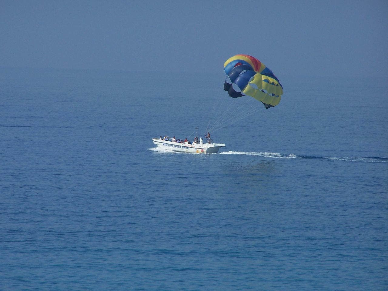 sea, nautical vessel, water, transportation, adventure, waterfront, leisure activity, nature, day, real people, outdoors, vacations, men, beauty in nature, scenics, extreme sports, horizon over water, blue, sailing, one person, sport, parachute, sky, jet boat, people