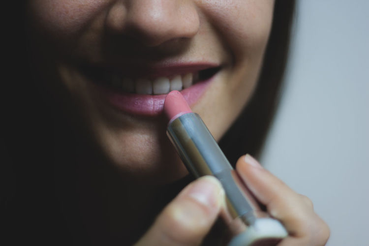 Close-Up Of Woman Applying Lipstick