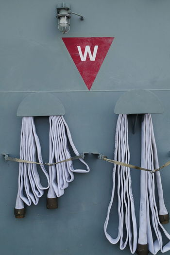 Close-up of white tied hanging on rope against wall
