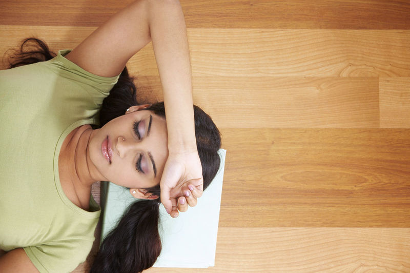 Directly Above Shot Of Young Woman Lying With Head On Book At Home