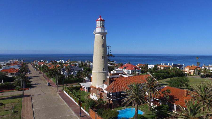 Lighthouse by sea against buildings against clear blue sky
