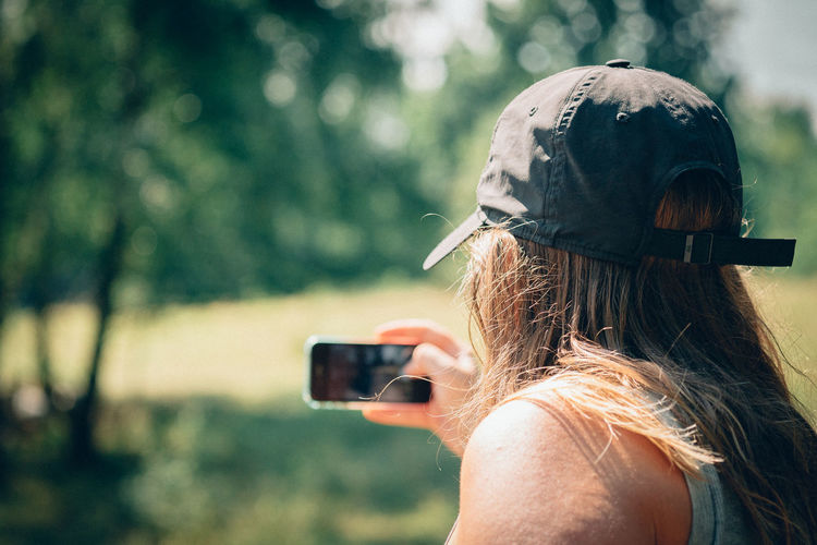 Rear view of man clicking selfie outdoors