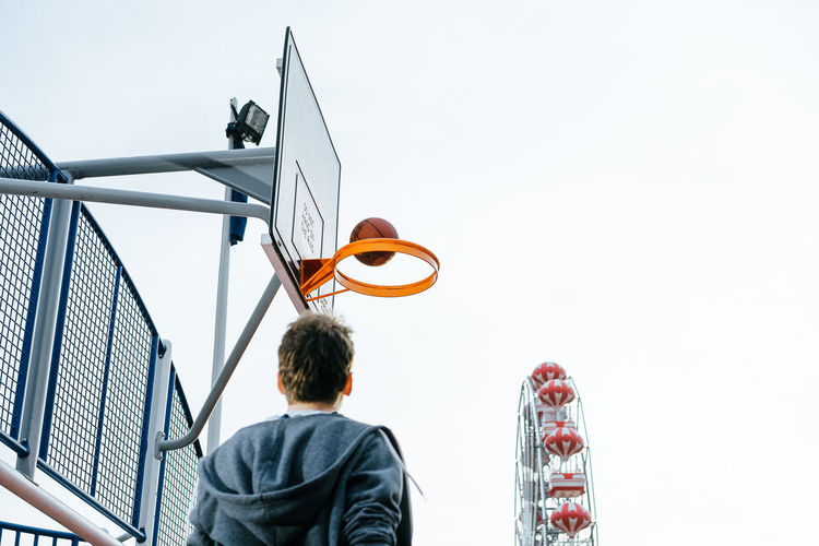 Basketball Basketball - Sport Basketball Hoop Basketball Player Basketball - Ball One Person One Man Only People Real People Men Rear View City Sky Hood - Clothing Wearing