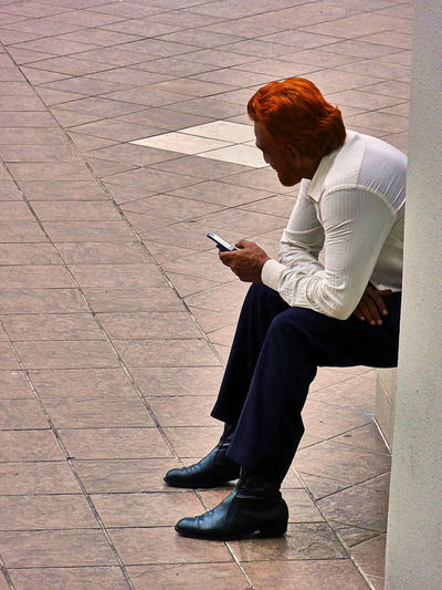 Beard Cellphone Enjoying Life Footwear Handy Hanging Out High Angle View Male Paving Stone People Person Real People Red Beard Red Hair Resting Shoes Sidewalk Sitting Sitting Outside Street Street Fashion Streetlife Taking A Break Thinking Tiled Floor