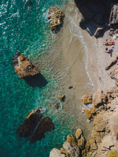 High angle view of rocks on beach with beach-goers tanning