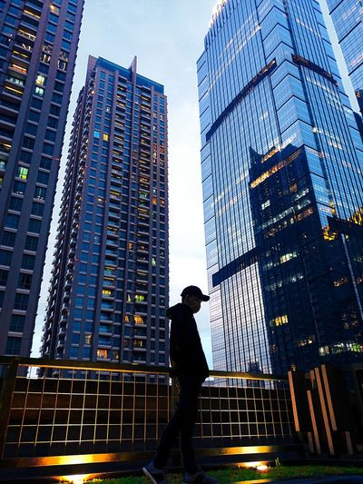 Low angle view of silhouette man standing by modern buildings in city against sky