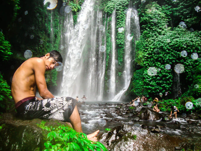 Side View Of Shirtless Man Sitting On Rock Against Waterfall In Forest
