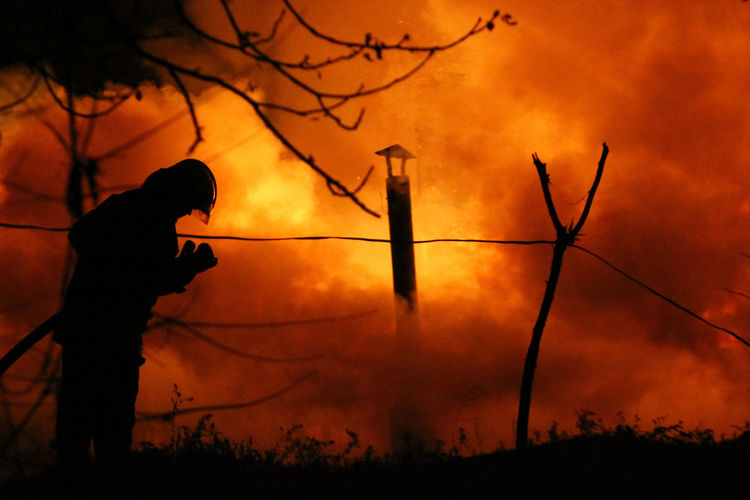 Firefighter Adult Fire Firefighter Forest Fire Hose Nature One Person Orange Color Outdoors People Real People Silhouette Standing The Photojournalist - 2017 EyeEm Awards Tree Focus On The Story The Photojournalist - 2018 EyeEm Awards