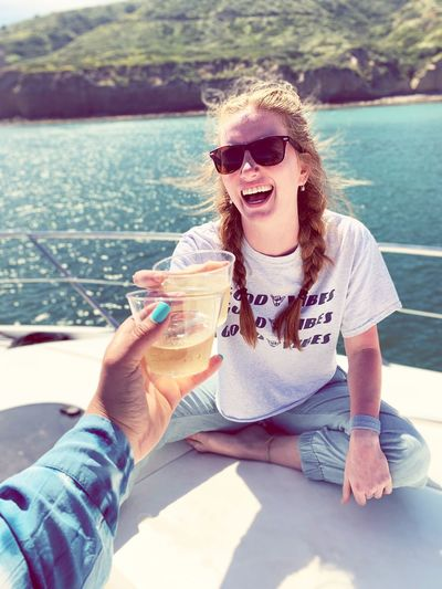 Cropped hand toasting drink with female friend on boat