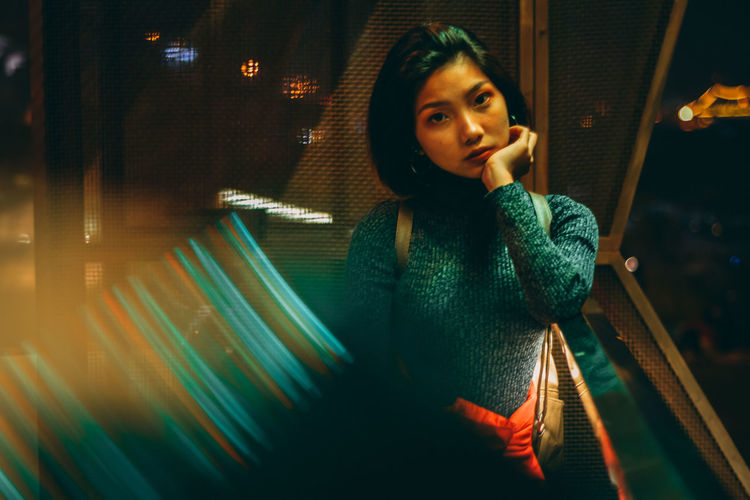 Nightlife Contemplation Beautiful Woman Lighting Equipment Window Portrait Standing Night Women Lifestyles Waist Up Looking Casual Clothing Looking Away Illuminated Young Women Indoors  Real People Front View Young Adult One Person Indoors  Leisure Activity Communication Technology