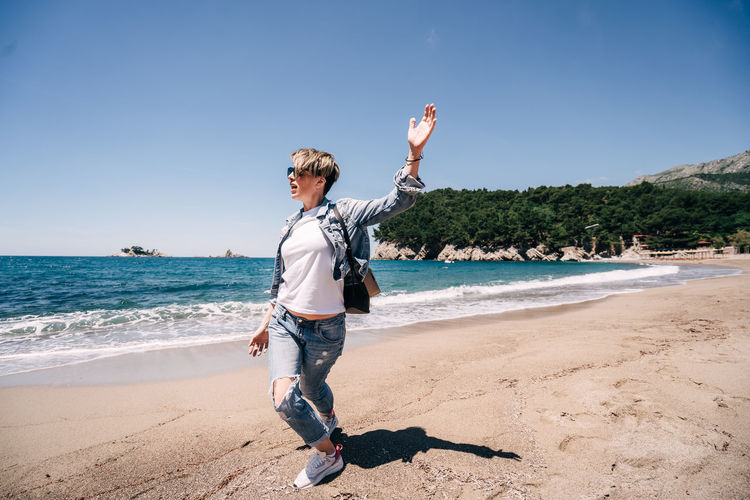 Girl with backpack on beach hands up person
