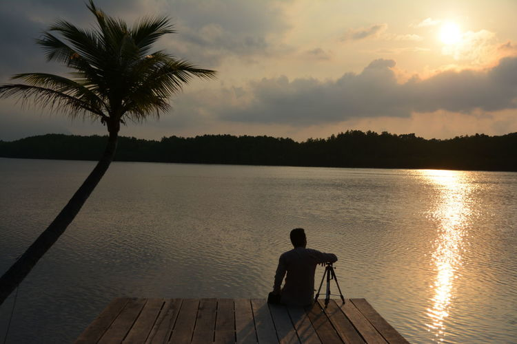 Rear view of silhouette man sitting by lake against sunset sky