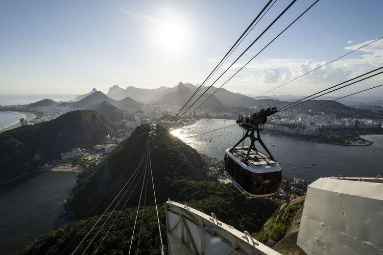 Overhead cable car over mountain against sky