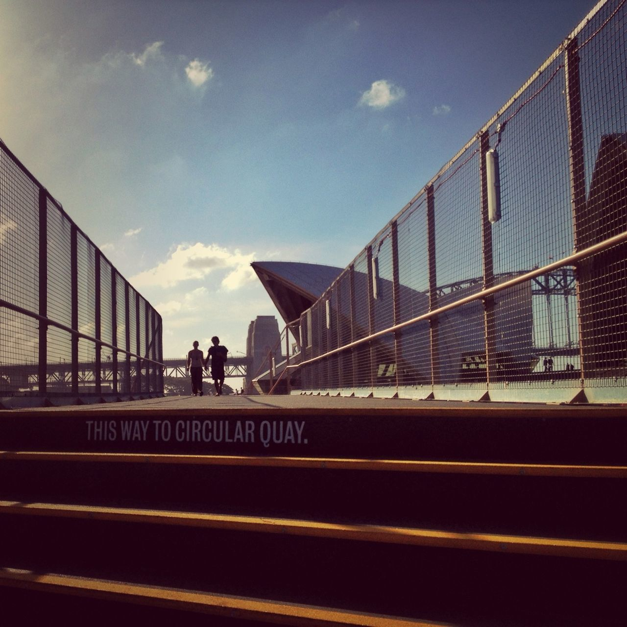 Couple walking on footpath against sydney opera house