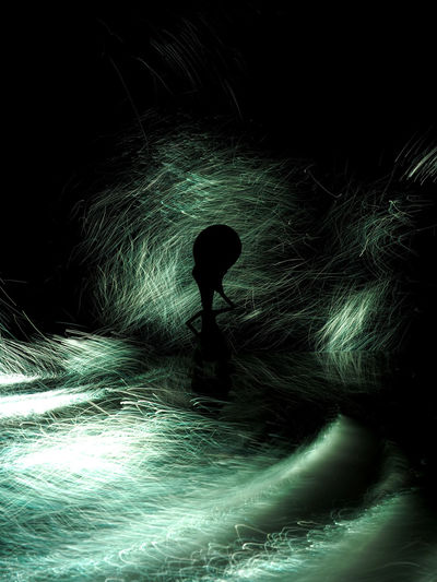 Silhouette of person standing in illuminated tunnel